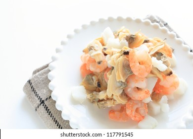 frozen mixed seafood on white dish with copy space