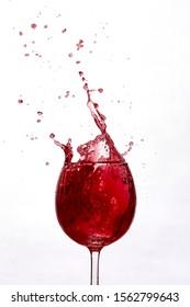 Frozen motion shot of wine splashing out of a wine glass.