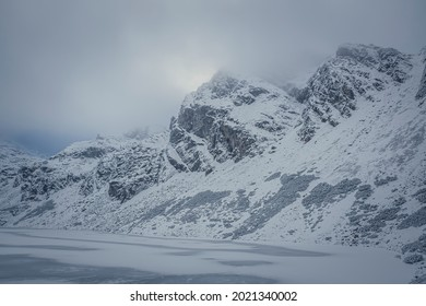Frozen mountain lake and rocky peak, High Tatras, Poland. Czarny Staw Gąsienicowy Pond and Kościelec Summit in the clouds. Selective focus on the crags, blurred background. - Shutterstock ID 2021340002