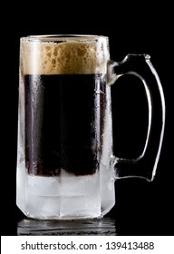 frozen mug with a stout style beer isolated on a black background