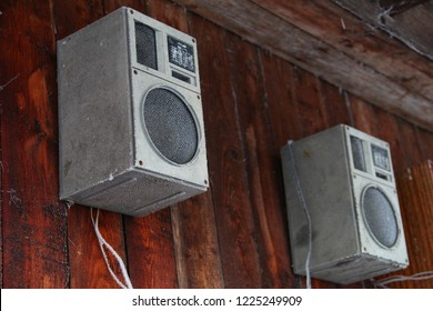 Frozen music speakers hang on the wooden wall of the house outdoors in the winter