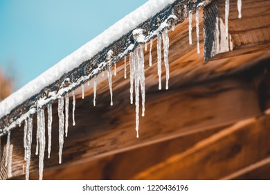 Frozen mysterious mansion with water pipe gutters  and frozen icicles on the roof, top floor wooden mansion. Icy weather winter scene