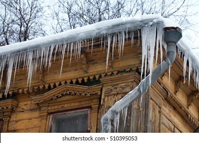 Frozen mysterious mansion with water pipe and frozen icicles on the roof, top floor wooden mansion. Icy weather winter scene