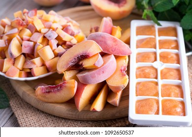 Frozen peaches on a wooden board (slices, slices, puree)
