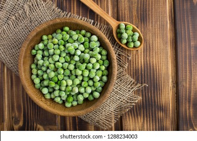 Frozen peas  in the brown bowl  on the  rustic wooden background.Top view.Copy space.Healthy food ingredient.