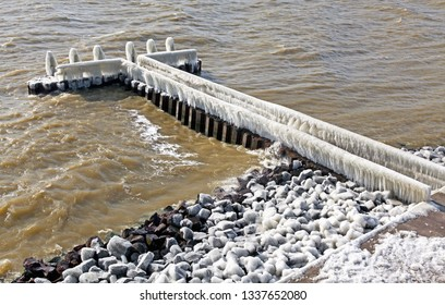 Frozen pier in Afsluitdijk - major causeway in Netherlands