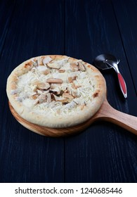 Frozen pizza with porcini and truffle, on a wooden board, set on a dark blue background