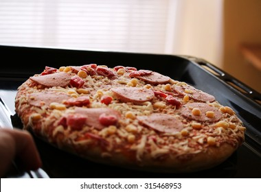 Frozen pizza with salami, cheese, corn and pepper