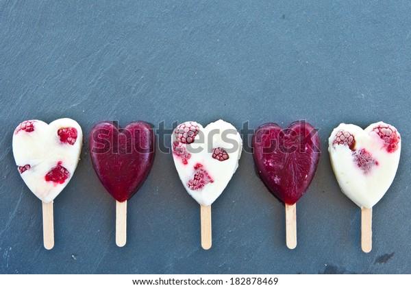 Frozen popsicle in heart-shape with fresh raspberries