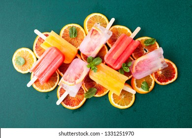 Frozen popsicles with fresh citrus fruits and mint leaves