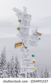 Frozen post with directions on the peak