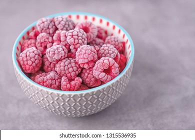 Frozen raspberries in a gray bowl on a gray beton background. Copy space