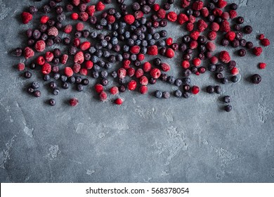 Frozen raspberry, blueberry, cranberry on grunge background. Frozen fruit. Flat lay, top view, copy space