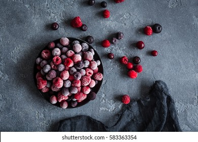 Frozen raspberry, blueberry, cranberry on dark background. Frozen fruit. Top view, flat lay.