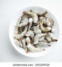 Frozen raw uncooked tiger prawns, shrimps set, on white stone surface, top view flat lay, square format