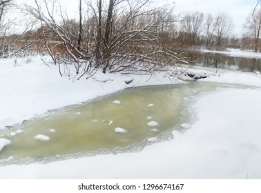 Frozen river with trees on the shore
