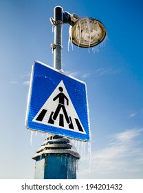 Frozen road sign for pedestrians with the street lamp above