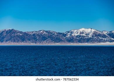 The frozen Sailimu lake with snow mountain background at Yili, Xinjiang of China.