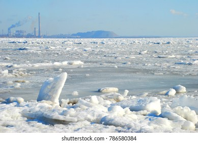 frozen sea in the background of the factory pipes