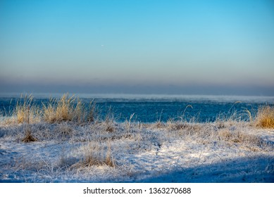 frozen sea beach in winter with low snow coverage. ice in sunny day on the beach
