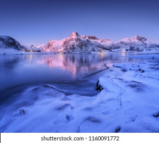 Frozen sea coast and beautiful snow covered mountains in winter at dusk. Beautiful fjord at night in Lofoten Islands, Norway. Nordic landscape with water, ice, rocks, buildings, illumination, blue sky