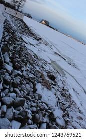 frozen sea Finn gulf snowed surface with low heavy clowds in pink sunset snowed rocks  wallpaper snowed background