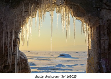 Frozen sea and through the arch with icicles