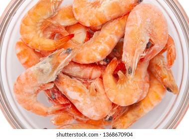 Frozen shrimp in a transparent bowl.
