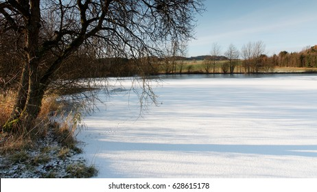 frozen snow covered pond in spring