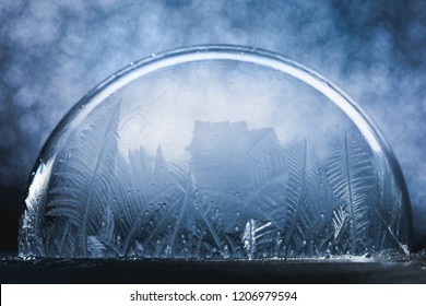 Frozen snow globe christmas magic ball with flying snowflakes. Winter Background. For Christmas and New Year Holidays precious backdrop. Ice patterns frosted on ball of soap against blue shiny