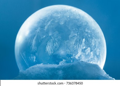 Frozen snow globe christmas magic ball with flying snowflakes. Winter Background. For Christmas and New Year Holidays precious backdrop. Ice patterns frosted on ball of soap against blue abstract