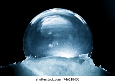 Frozen snow globe christmas magic ball with flying snowflakes. Winter Background. Christmas and New Year Holidays precious backdrop. Ice patterns frosted on ball of soap against dark black abstract