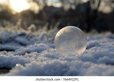 frozen soap bubble on a snow covered meadow in the sunset