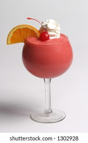 Frozen strawberry cocktail with whipped cream, orange and cherry garnish.