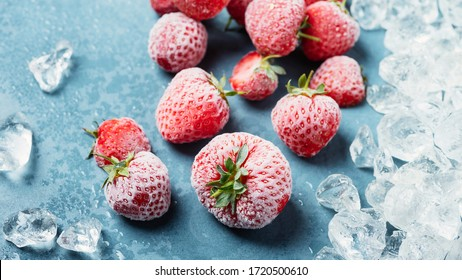 Frozen strawberry with crystals of ice on the blue background, selective focus image and slider format