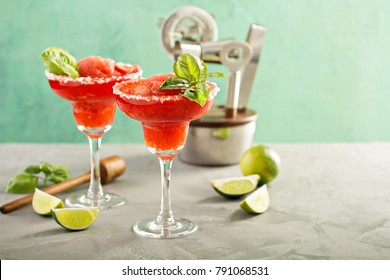 Frozen strawberry lime basil margarita in tall footed glasses