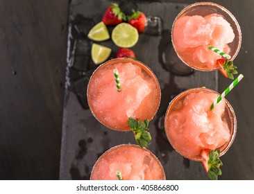Frozen strawberry margarita cocktail in margarita glass.