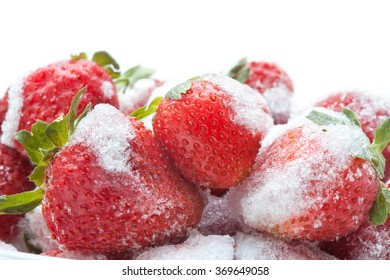 Frozen strawberry on white background. Macro view, detailed seeds and snowflakes. Soft focus
