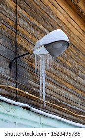 Frozen street lamp with hanging icicles. Vintage wooden wall of a house with an attached night lighting device covered by snow and pieces of ice.