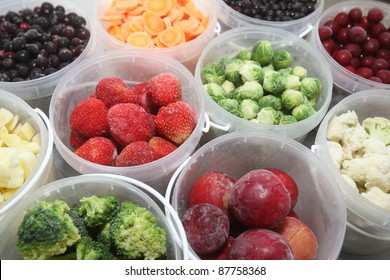 Frozen summer fruits and healthy vegetables in plastic containers
