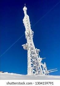 Frozen telecommunication antenna covered with ice and snow during cold winter against clear blue sky