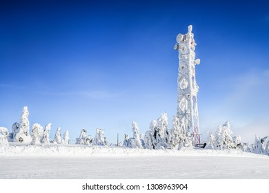 Frozen television or cellular tower in heavy snow near ski center. Telecommunication towers with dish and mobile antenna against blue sky in winter mountains.