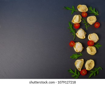 Frozen tortellini on the black background. Italian tortellini with fresh ricotta leaves and tomatoes on a black stone board. Top view. Italian tortellini with fresh ricotta leaves and tomatoes