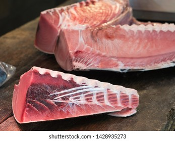 Frozen tuna being carved at the fish market