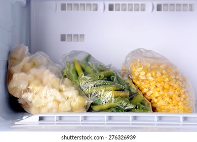 Frozen vegetables in bags in freezer close up