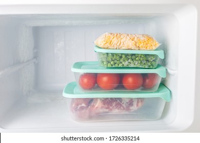 Frozen vegetables and meat in blue plastic containers. Frozen corn, peas, tomatoes, meat. Cold freezer. Empty space for text.