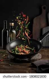 Frozen vegetables: a mixture of vegetables, string beans and cauliflower is poured into a black pan on a dark background. Flying food close-up with a copyspace. Vertical orientation.