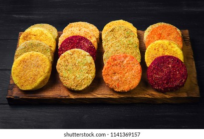 Frozen Vegetables patties (cutlets) for vegan burgers in bowl. Mix Vegetables stack fresh burgers. Spices for Vegetables patties (cutlets) thyme, arugula. Gray wooden background.