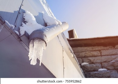 frozen water in a drainpipe, with hanging icicles