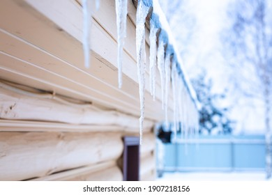 Frozen water on the roof. Icicles. Ice on the roof of the house. High quality photo